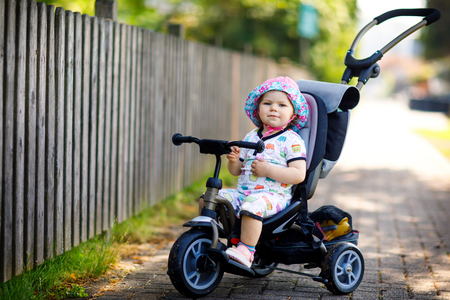 Cute adorable toddler girl sitting on pushing bicyle or tricycle. Little baby child going for a walk with parents on sunny day. Stock Photo