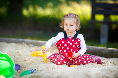 Cute toddler girl playing in sand on outdoor playground. Beautiful baby in red gum trousers having fun on sunny warm summer day. Standard-Bild