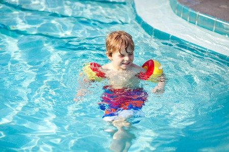 Happy little kid boy having fun in an swimming pool. Active happy preschool child learning to swim. with safe floaties