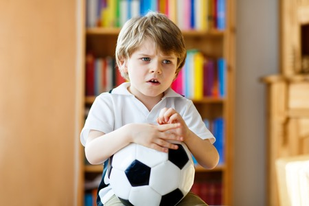 Sad and not happy little kid with football about lost football or soccer game. child after watching match on tv Stock Photo