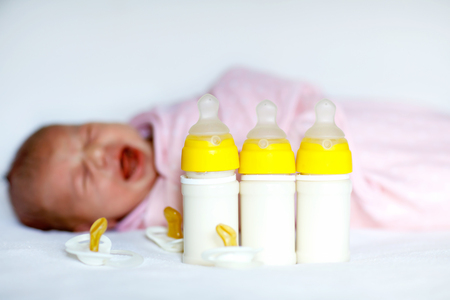 Crying newborn baby girl with nursing bottles. Formula drink for babies. Banco de Imagens