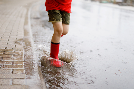 Child wearing red rain boots jumping into a puddle.