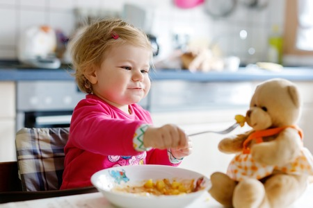 Adorable baby girl eating from fork vegetables and pasta. Little child feeding and playing with toy teddy bear. Cute toddler, daughter with spoon sitting in highchair and learning to eat by itself