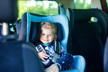 Adorable baby girl with blue eyes sitting in car safety seat. Toddler child going on family vacations and jorney. Smiling happy child during traffic jam Foto de archivo - 110846496