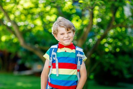 Fröhlicher kleiner Junge in buntem Hemd und Rucksack oder Schultasche an seinem ersten Tag in der Schule oder im Kindergarten. Kind im Freien an einem warmen sonnigen Tag, Zurück zum Schulkonzept. Junge in bunter Uniform