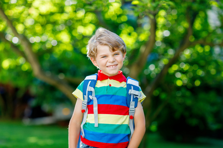 Happy little kid boy in colorful shirt and backpack or satchel on his first day to school or nursery. Child outdoors on warm sunny day, Back to school concept. Boy in colorful uniform