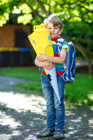 Happy little kid boy in colorful shirt and backpack or satchel and traditional German school bag cone called Schultuete with gifts on his first day to school. Child outdoors on warm sunny day Stockfoto
