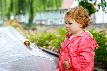 Cute adorable baby girl discovering snail on a walk. Beautiful curly toddler child having fun on rainy day. With big umbrella, child in waterproof clothes Stock Photo