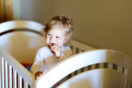 Cute little baby girl lying in cot after sleeping. Healthy happy child in bed climbing out. Stock Photo