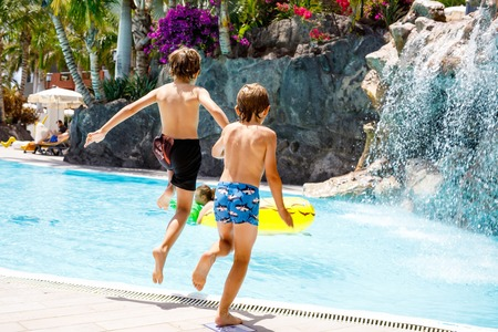 Two happy little kids boys jumping in the pool and having fun on family vacations in a hotel resort. Healthy children, siblings and best friends Stock Photo