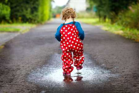 Close-up of little toddler girl wearing rain boots and trousers and walking during sleet, rain on cold day. Baby child in colorful fashion casual clothes jumping in a puddle Stock Photo