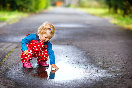 Close-up of little toddler girl wearing rain boots and trousers and walking during sleet, rain on cold day.