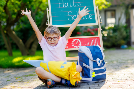 Happy little kid boy with glasses sitting by desk and backpack or satchel. Schoolkid with traditional German school bag cone called Schultuete on his first day to school