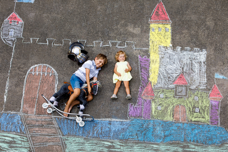 Little active kid boy and cute toddler baby girl drawing knight castle and fortress with colorful chalks on asphalt. Happy children with helmet and rocking horse toy having fun with playing knight.