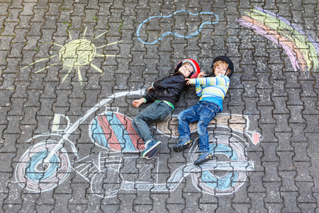 Creative leisure for children: two little funny friends in helmet having fun with motorcycle picture drawing with colorful chalks. Children, lifestyle, fun concept Stock Photo