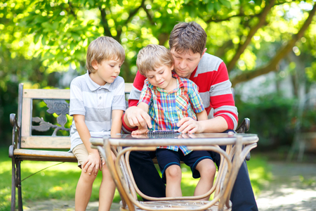 Two little kid boys and father playing together checkers game Standard-Bild - 105996764
