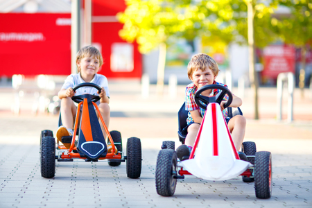 Two active little kid boys driving pedal race car in summer garden, outdoors. Children, best friends racing with fast speed and having fun.