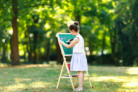 Happy little kid girl standing by big chalk desk Preschool or schoolkid on first day of elementary class. Back to school concept. Healthy child writing and painting on desk outdoors. Copyspace on desk
