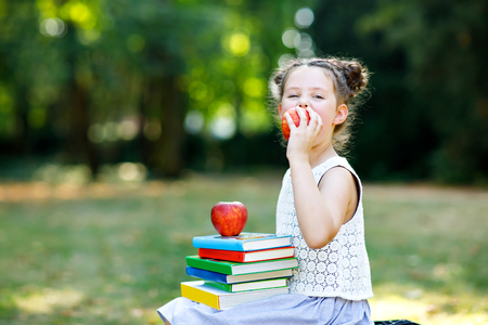 Happy adorable little kid girl reading book and holding different colorful books, apples and glasses on first day to school or nursery. Back to school concept. Healthy child of elementary class. Foto de archivo - 106238117