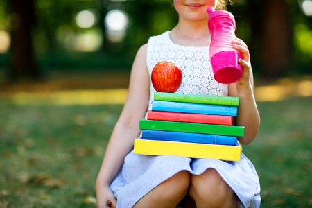 Happy adorable little kid girl reading book and holding different colorful books, apples and water bottle on first day to school or nursery. Back to school concept. Healthy child of elementary class.