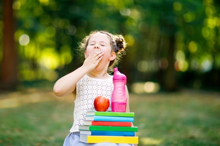 Tired adorable little kid girl reading book and holding different colorful books, apples and pencils on first day to school or nursery. Back to school concept. Healthy child of elementary class.