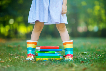 Closeup of legs of school girl in rubber boots and different colorful books on green grass. first day to school or nursery. Child outdoors , Back to school concept. Healthy child of elementary class