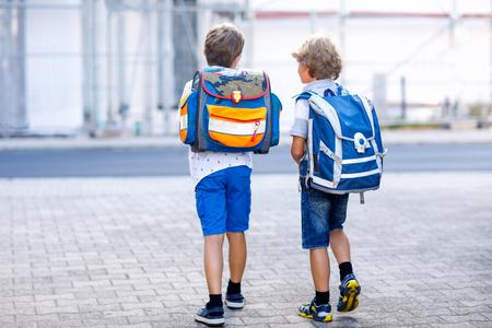 Zwei kleine Jungen mit Rucksack oder Schulranzen. Schulkinder auf dem Weg zur Schule. Gesunde entzückende Kinder, Brüder und beste Freunde draußen auf der Straße, die das Haus verlässt. Zurück zur Schule. Glückliche Geschwister.