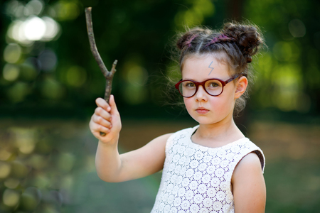 Funny adorable little kid girl with glasses and wooden magic wand playing Harry Potter in park on sunny day.