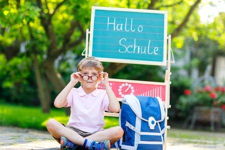 Szczęśliwy mały chłopiec w okularach siedzi przy biurku i plecaku lub tornister