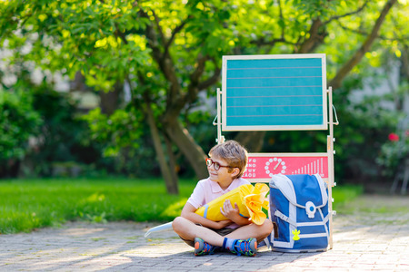 Happy little kid boy with glasses sitting by desk and backpack or satchel Imagens