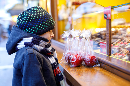 Little cute kid boy near sweet stand with sugared apples and chocolate fruits