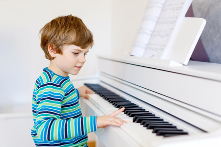 Cute healthy little kid boy playing piano in living room or music school. Preschool child having fun with learning to play music instrument. Education, skills concept Standard-Bild - 106975355