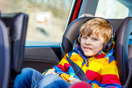 Healthy little blond kid boy watching tv or dvd with headphones during long car driving on family vacations. Leisure for children for long drive. Preschool child sitting in safe car seat Stock Photo