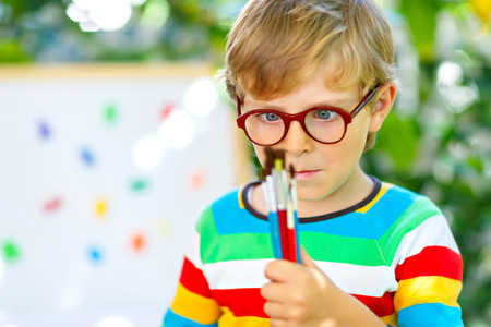 Confused little kid boy with glasses holding watercolors and brushes. Happy child and student is back to school. Education, school, learning concept. School, preschool nursery equipment.