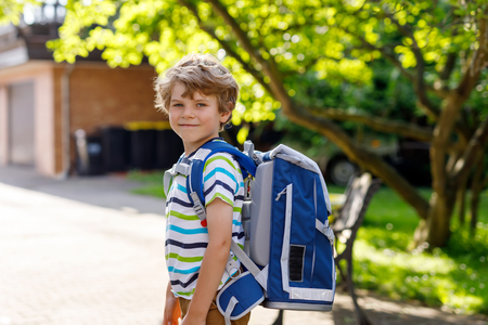 Happy little kid boy with glasses and backpack or satchel on his first day to school or nursery. Child outdoors on warm sunny day, Back to school concept: Stock Photo