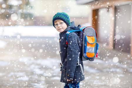 Little school kid boy of elementary class walking to school. Happy child having fun and playing with first snow. Student with backpack in colorful winter clothes. School building: Archivio Fotografico