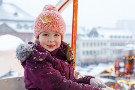 Little cute kid girl having fun on ferris wheel on traditional German Christmas market during strong snowfall. Happy child enjoying family market in Germany, Munich. Laughing girl on carousel: