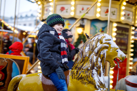 Adorable little kid boy riding on a merry go round carousel animal at Christmas funfair or market, outdoors. Happy child having fun on traditional family xmas market in Berlin, Germany Imagens