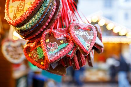Gingerbread Hearts at German Christmas Market. Nuremberg, Munich, Berlin, Hamburg xmas market in Germany. On traditional ginger bread cookies written Happy Holiday called Lebkuchenherz in German Archivio Fotografico - 107100915