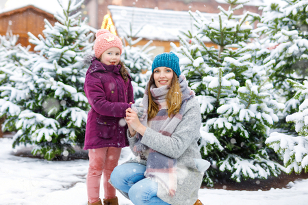 Cute little smiling kid girl and mother on christmas tree market. Happy child, daughter and young woman in winter clothes choosing xmas tree on xmas market with lights on background on winter day Stock Photo