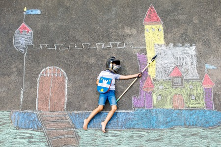 Little active kid boy drawing knight castle and fortress with colorful chalks on asphalt. Happy child in helmet and with spear having fun with playing knight game and painting
