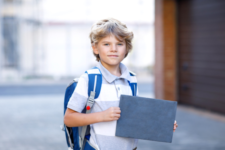 Happy little kid boy with backpack or satchel. Schoolkid on the way to school. Healthy adorable child outdoors With empty chalk desk for copyspace. Back to school.