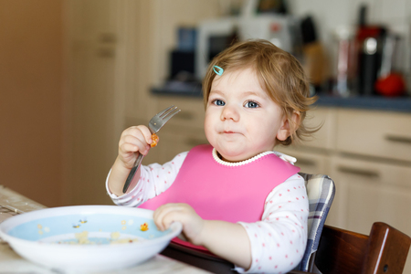 Adorable baby girl eating from spoon mashed vegetables and puree. food, child, feeding and development concept -cute toddler, daughter with spoon sitting in highchair and learning to eat by itself.