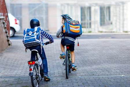 Due ragazzi del bambino della scuola in casco di sicurezza in sella con la bici in città con gli zaini. Bambini felici in abiti colorati in bicicletta sulle biciclette sulla strada per la scuola. Modo sicuro per i bambini all'aperto a scuola