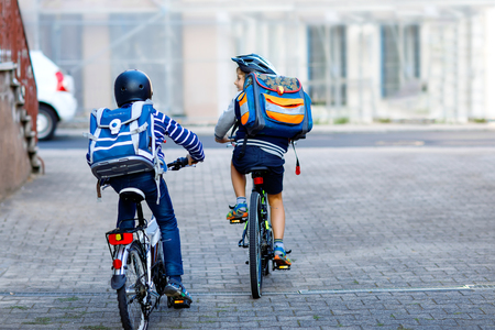 Two school kid boys in safety helmet riding with bike in the city with backpacks. Happy children in colorful clothes biking on bicycles on way to school. Safe way for kids outdoors to school