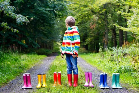 Little kid boy and group of colorful rain boots. Blond child standing in autumn forest. Close-up of schoolkid and different rubber boots. Footwear and fashion for rainy fall Foto de archivo - 107442576