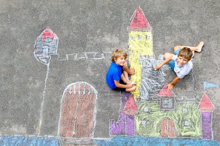 Due ragazzini di bambini che disegnano il castello del cavaliere con gessetti colorati su asfalto. Fratelli e amici felici che si divertono con la creazione di immagini e dipinti in gesso. Tempo libero creativo per i bambini in estate.