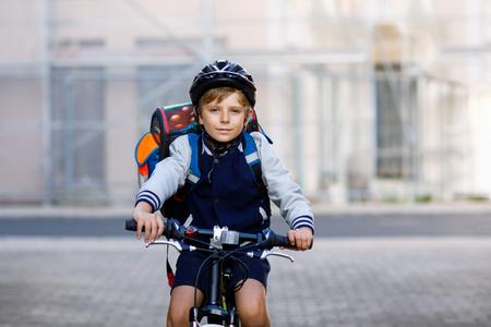 Schulkindjunge im Schutzhelm, der mit Fahrrad in der Stadt mit Rucksack reitet. Glückliches Kind in den bunten Kleidern, die auf Fahrrad auf dem Weg zur Schule radeln. Sicherer Weg für Kinder im Freien zur Schule Standard-Bild