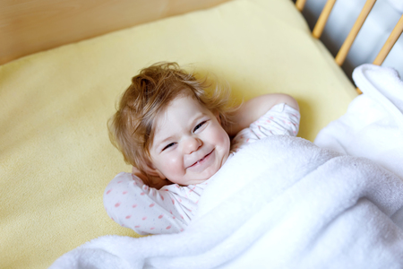 Cute little baby girl lying in cot before sleeping. Happy calm child in bed. Going sleep. Peaceful and smiling child looking on parents. Going to bed alone