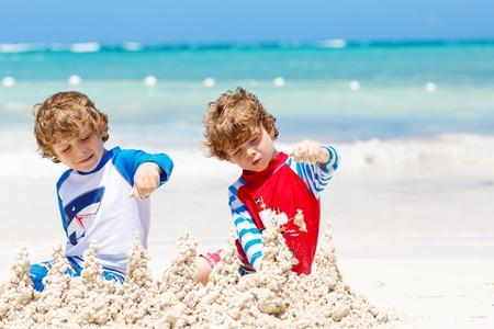 Two kid boys building sand castle on tropical beach of Playa del Carmen, Mexico